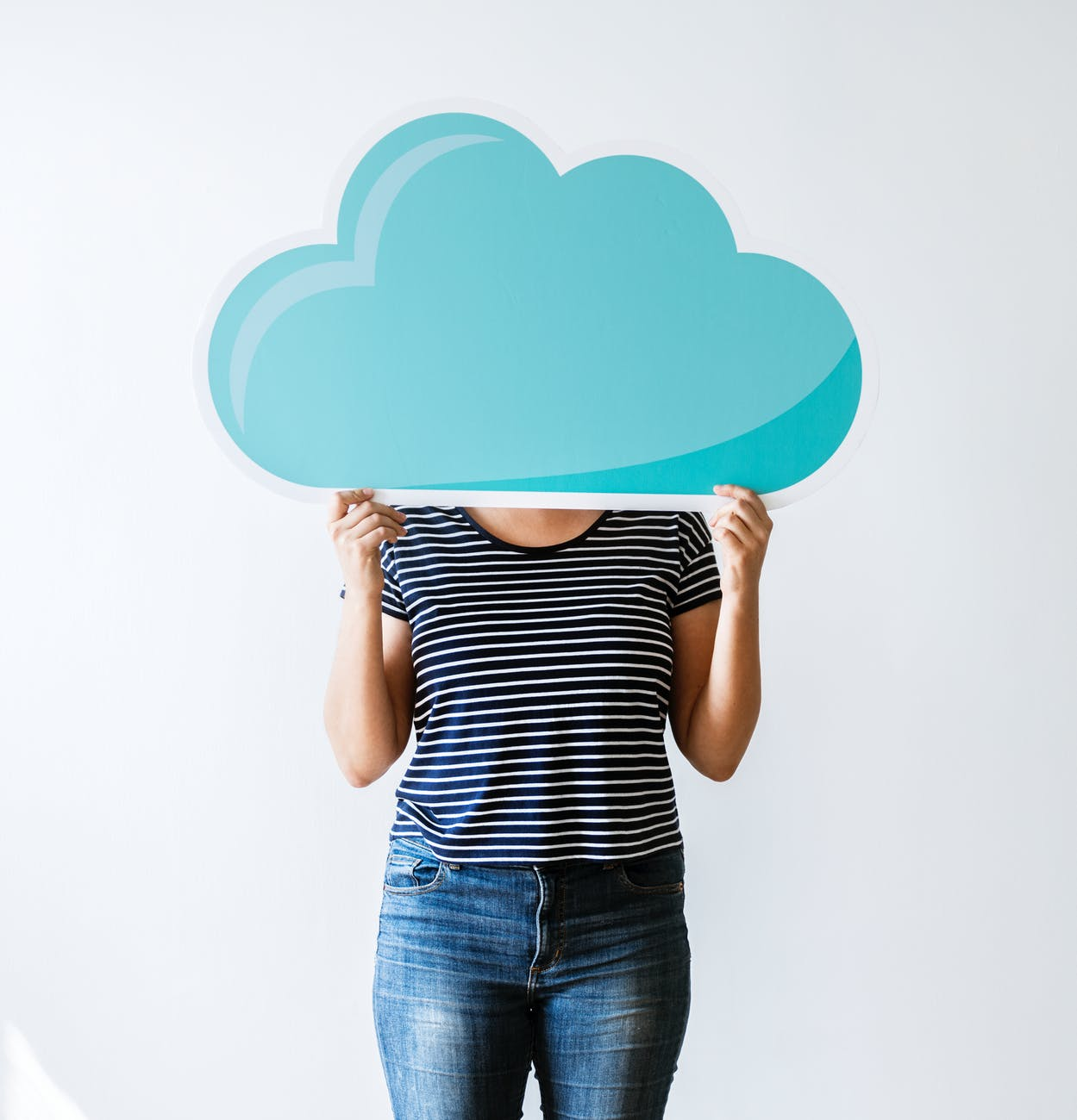 person covering face with blue wooden cloud wall decor